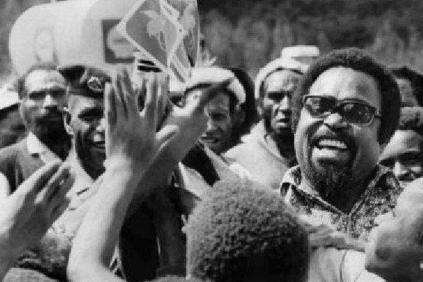 Sur cette photo de 1974, Sir Michael Somare, qui allait devenir le tout premier Premier ministre de la Papouasie Nouvelle-Guinée, agite le drapeau de son pays sur le point de devenir indépendant, en compagnie des élèves d'une école. (Denis Williams' estat