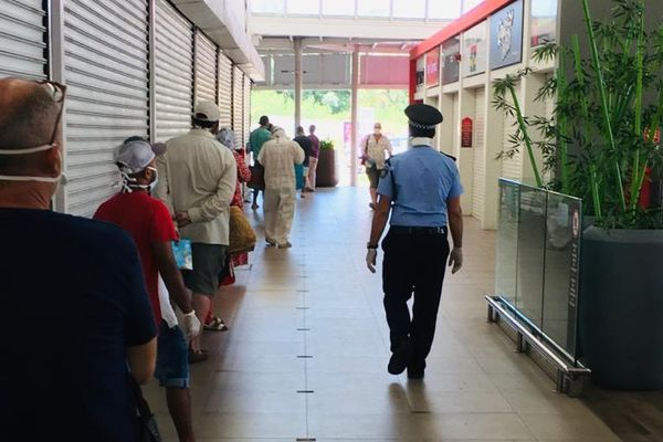 File d'attente supermarché île Maurice avec policier