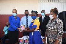 À la Jamaïque, le ministre de l'Éducation, Fayval Williams (à gauche) distribue des tablettes dans des écoles.