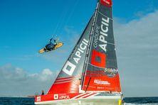 La petite planche du kitesurfeur face à l'immense Imoca 60 pieds du marin