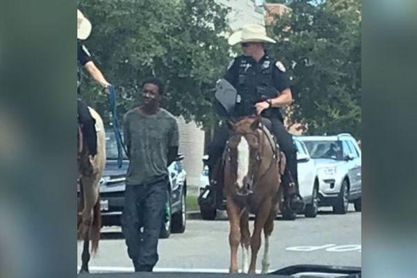 Un Noir arrêté et tenu par une corde par des policiers à cheval