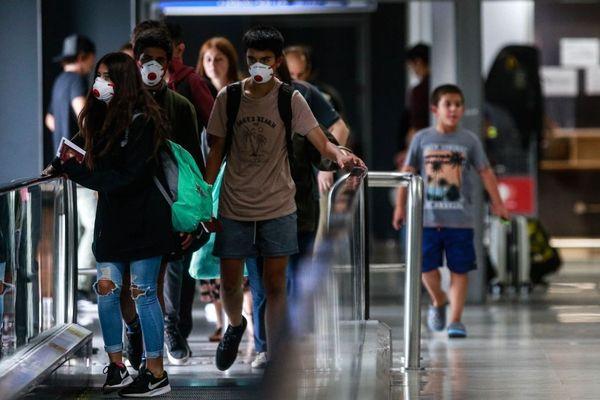 Des voyageurs avec des masques de protection, à l'aéroport de Cumbica, à Sao Paulo.