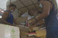Les agents du centre de tri de l'OPT à Faa'a dépotent un container de colis.