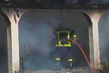 Un pompier de Faa'a tente de venir à bout des flammes qui ravagent une des quatre maisons.