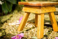 Un tabouret fabriqué avec une assise en wassaï et des pieds en bois