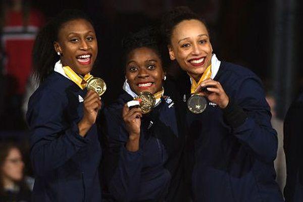 La capitaine Siraba Dembele, Grace Zaadi et Béatrice Edwige posent avec leurs médailles après avoir battu la Norvège en finale le 17 décembre