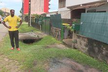 Le locataire devant le trou où s'écoulent les eaux usées à l'avenue Pasteur à Cayenne
