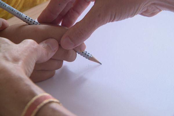 Une main tient un crayon, écrire, graphopédagogie