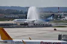 """Le nouvel avion de la compagnie Corsair reçoit le """"water salute"""", un """"baptême"""" qui marque sa mise en circulation."""