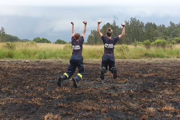 Des volontaires pompiers montrent leur joie qu'il pleuve, dans la région de Hunter.