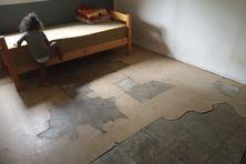 Les dalles du sol de cet appartement se décollent depuis les inondations.