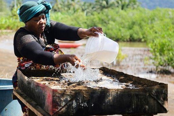 Dame versant de l'eau à Bandrélé