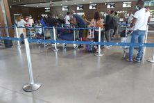 Les passagers dans la file d'attente pour les formalités d'embarquement à l'aéroport de Pamandzi