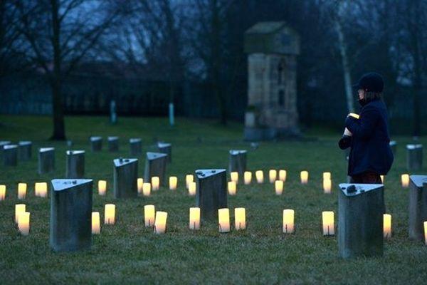 27 janvier 2015, au cimetière juif d'Auschwitz, un enfantd épose une bougie en mémoire des victimes de la Shoah