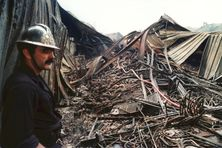 Photo prise le 27 février 1991 à Saint-Denis de La Réunion, d'un pompier regardant les restes de l'entrepôt FO-YAM détruit à la suite des émeutes du 25 février dans le quartier du Chaudron.