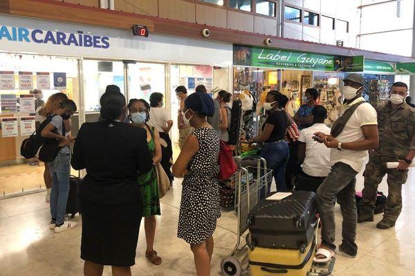Des passagers en quête d'information devant les comptoirs des compagnies