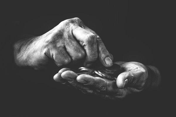 Pauvreté main avec pièces de monnaie