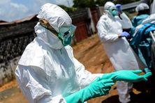 Une équipe de la Croix-Rouge s'équipe avant une intervention à Monrovia (Liberia), le 10 octobre 2014. (MOHAMMED ELSHAMY / ANADOLU AGENCY / AFP)