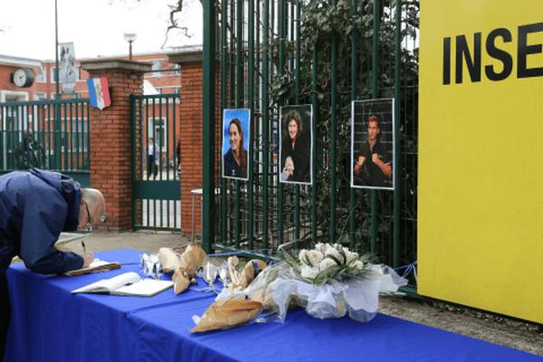Des photos, des fleurs et des cahiers à l'entrée de l'Insep