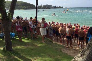 Les concurrents avant le départ sur la plage et, sur l'eau, la sécurité.