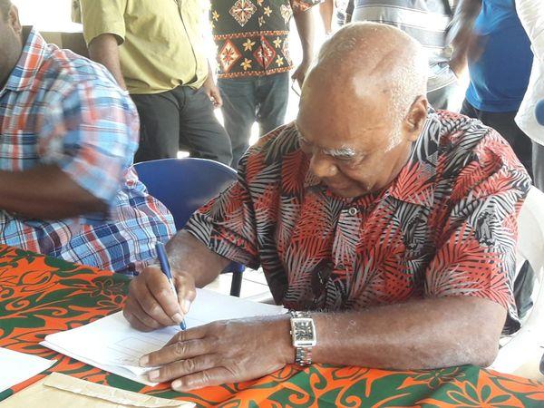 Hilarion Vendegou, grand chef et maire de l'île des Pins, signant le protocole coutumier autour du futur câble Tomoo, 29 novembre 2019