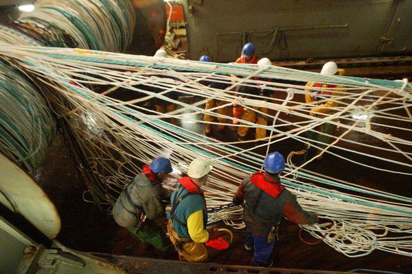 Les ramendeurs d'un chalutier-industriel à la manoeuvre du chalut-pélagique