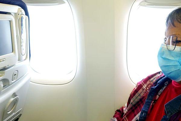 voyageurs avec masque en avion