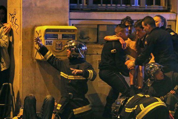 Des pompiers s'occupent de blessés devant la salle de concert Le Bataclan, à Paris, vendredi 13 novembre 2015.