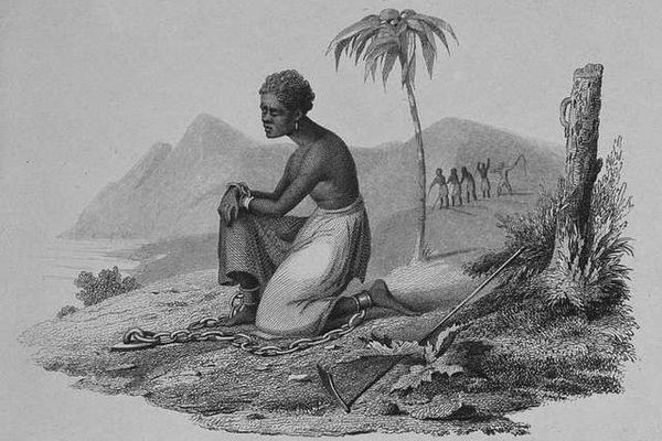 Female in chains kneeling on the ground in a plantation