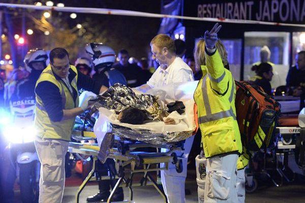 Des personnes évacuent une personne blessée du Bataclan