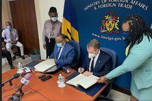 À Barbade, Jerome Walcott (à gauche) ministre des affaires étrangères de Barbade et Stephen Kavanaugh, directeur des service de police de l'INTERPOL, signent l'accord pour inaugurer un nouveau bureau à Bridgetown.