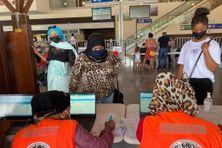 Les voyageurs faisant la queue devant l'un des stands de dépistage d'urgence à l'aéroport de Pamandzi