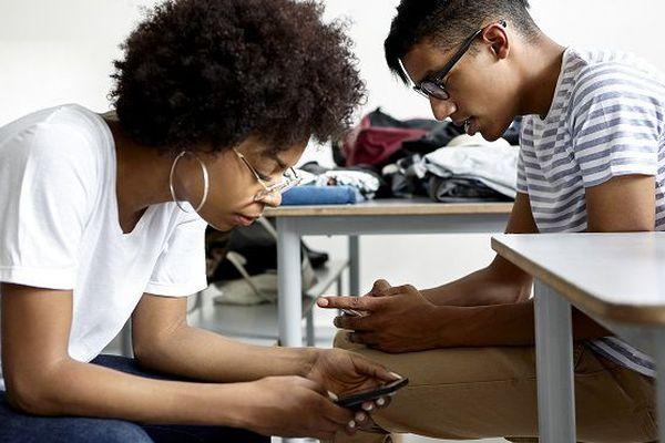 Deux étudiants regardent leur téléphone portable.