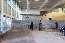 Les ouvriers en train de démonter le carrelage du hall principal de l'aéroport Pointe- Blanche.