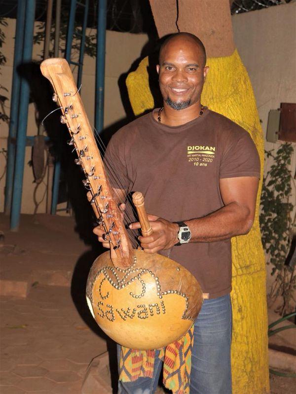 Yannick Théolade avec une Kora, instrument traditionnel offert par un Griot, maître de Kora