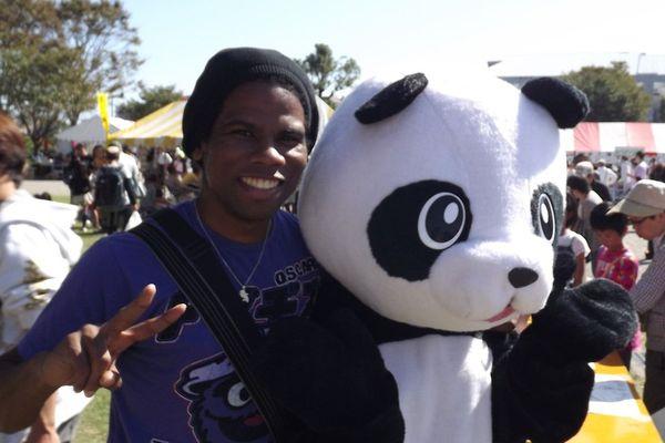 """Gérald René-Corail et une mascotte """"Panda"""" lors d'une fête municipale."""