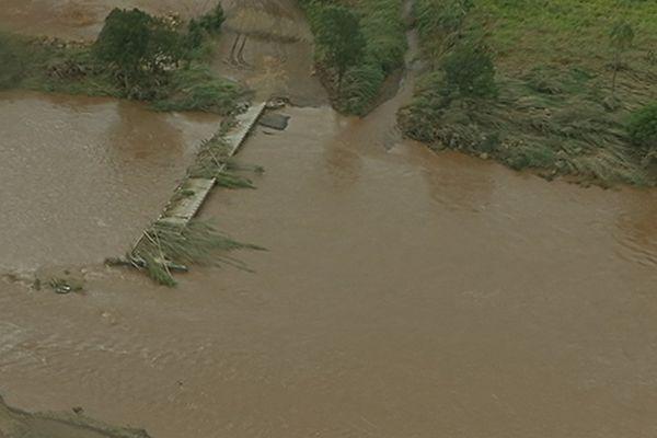 Une partie du pont a été emporté par la rivière.