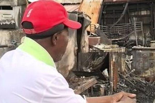 Serge Touloupe devant les décombres de la maison incendiée cité Mango