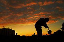 La silhouette d'un fossoyeur, portant une tenue de protection, se détache sur le coucher de soleil alors qu'il creuse une tombe pour une victime du Covid-19, le 28 mai 2020 à Rio de Janeiro au Brésil.