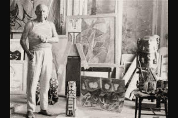 La statue du Dieu A'a à droite sur la photo dans laquelle pose Pablo Picasso
