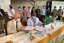 Le préfet (veste beige) signe l'engagement de l'État avec le maire de Rivière Pilote (chemise bleue).