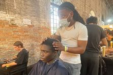Le barber guyanais Nicolas Bravo à l'oeuvre au éfilé de Men's &Couture Show de la Maison Valentino en Italie