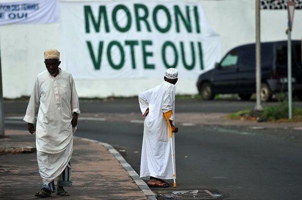 Un homme s'approche d'une banderole appelant à un 'oui' lors du prochain référendum constitutionnel le 27 juillet 2018 à Moroni.