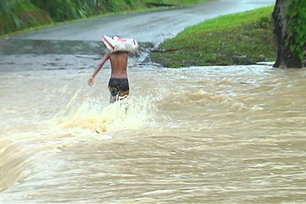 Un jeune homme traverse une rivière en crue
