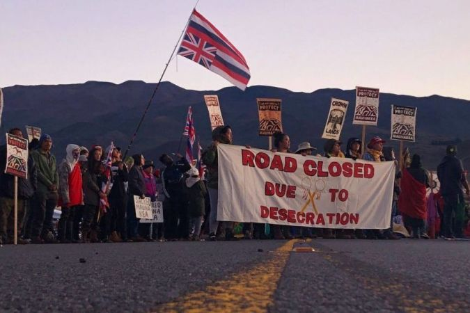 Des manifestants bloquent la route, aux pieds de la plus haute montagne de Hawaii. © Photo credit Caleb Jones/AP